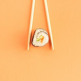 Sushi-rollen und essstäbchen, lokalisiert auf orange