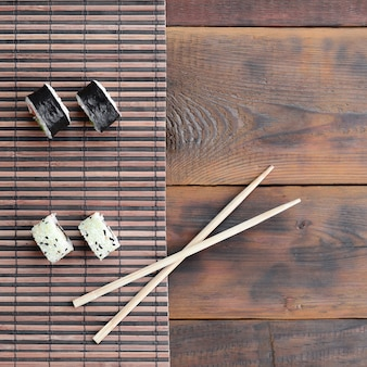 Sushi-rollen und hölzerne essstäbchen liegen auf einer bambus-stroh-serwing-matte. traditionelles asiatisches essen. ansicht von oben