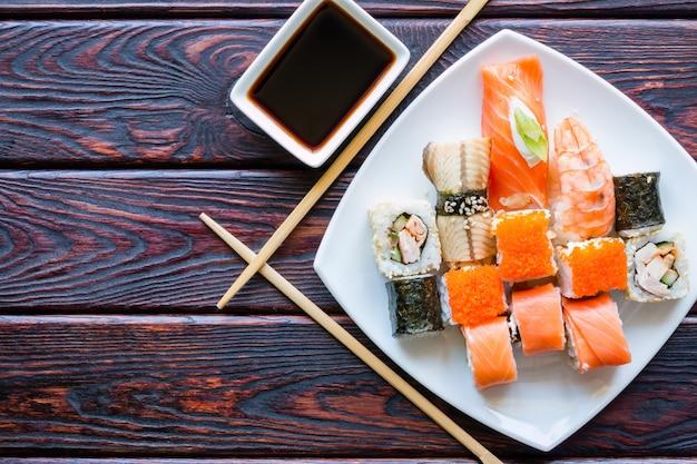 Sushi rollt auf einem weißen teller und essstäbchen
