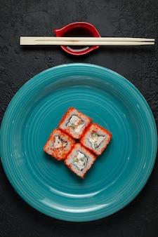 Sushi rollt in der grünen platte auf einem dunklen steinhintergrund mit bambusstöcken und sojasauce