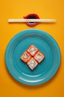 Sushi rollt in der grünen platte auf gelbem hintergrund mit bambusstöcken und sojasauce