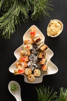 Sushi-satz diente in platte als weihnachtsbaum mit festlicher dekoration auf schwarzem hintergrund. von oben betrachten.
