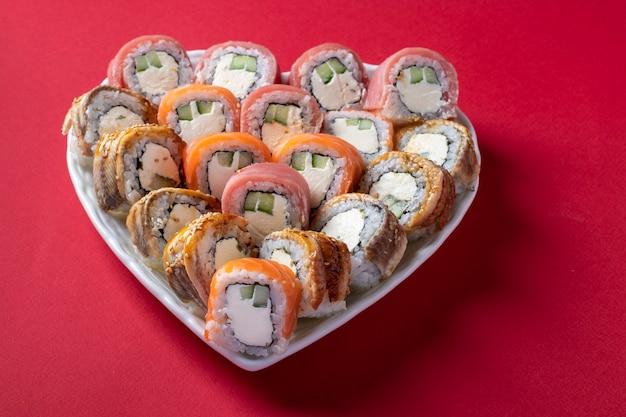 Sushi-satz von lachs, thunfisch und aal mit philadelphia-käse in platte als herz auf rotem hintergrund. valentinstag food-konzept. nahansicht