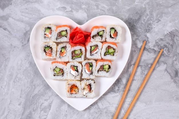 Sushi-set aus lachs-thunfisch mit philadelphia-käse in herzförmigen gerichten