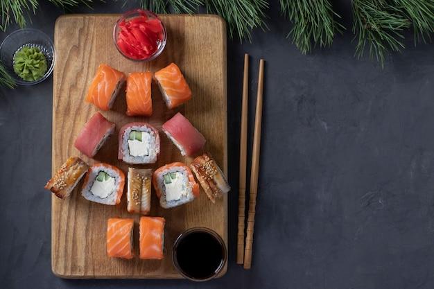 Sushi-set aus lachs, thunfisch und aal als weihnachtsbaum serviert auf einem holzbrett als weihnachtsdekoration auf dunklem hintergrund. platz für text
