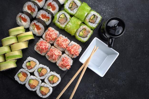 Sushi-set aus verschiedenen brötchen mit kaviar aus fliegenden fischen, tobiko, garnelen, aal, lachs, avocado, stöcken und sojasauce