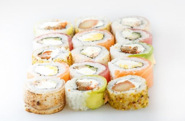 Sushi-set. brötchen mit lachs und gemüse, vegetarisch, auf einer holzplatte isoliert auf weißer oberfläche