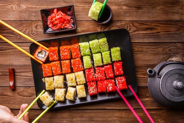 Sushi set brötchen mit sojasauce auf schwarzem teller serviert