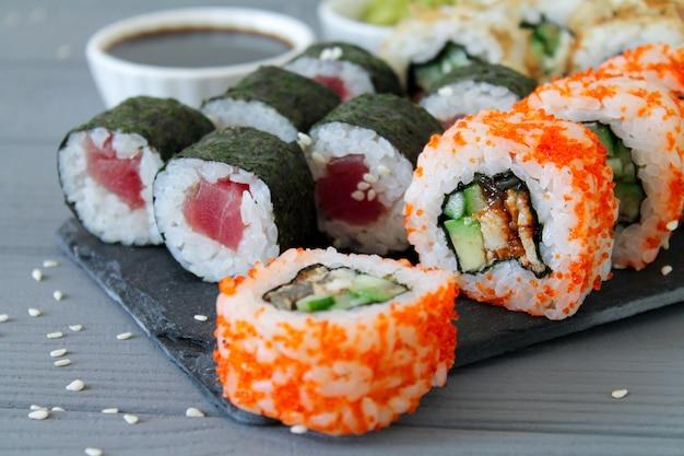 Sushi-set california und maki rollen auf steinbrett