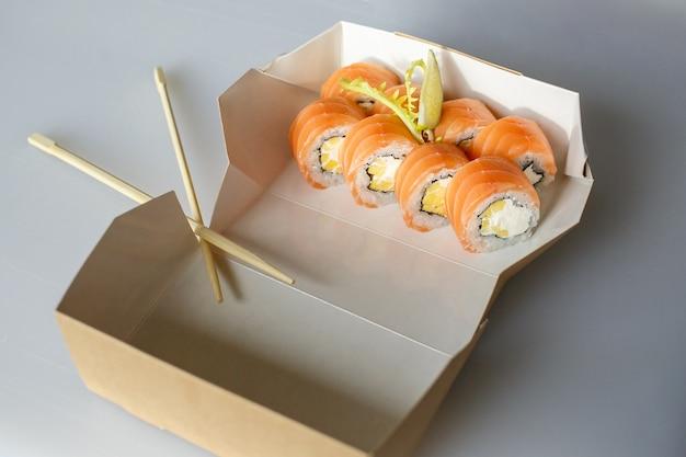 Sushi-set, japanisch, ingwer und wasabi, in einer schachtel, auf weißer oberfläche mit stäbchen