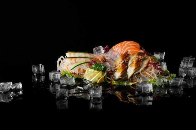 Sushi-set mit schmelzenden eisstücken auf schwarzem hintergrund mit reflexion