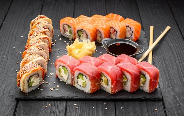 Sushi-set nigiri und sushi-rollen auf schwarzem stein schiefer serviert