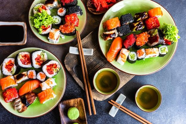 Sushi set sashimi und sushi-rollen auf steinschiefer serviert