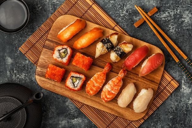 Sushi-set: sushi und sushi-rollen auf holzteller.