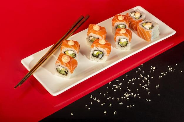 Sushi setzt nigiri, uramaki, kalifornien, philadelphia, auf einen weißen teller. auf einem roten hintergrund. speicherplatz kopieren.
