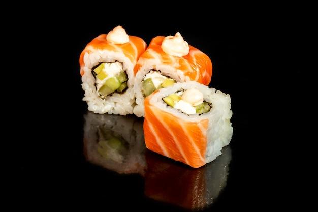 Sushi setzt uramaki, kalifornien, philadelphia, auf einen weißen teller. festliches neujahrskonzept. vor einem dunklen reflektierenden hintergrund. speicherplatz kopieren