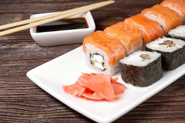 Sushi-sortiment auf weißem teller auf braunem holztisch