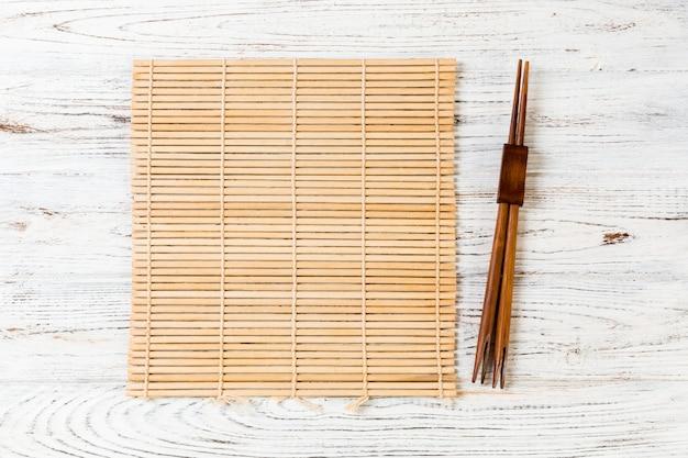 Sushi-stäbchen mit leerer brauner bambusmatte