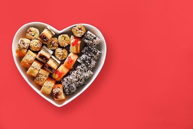 Sushi stellte in platte als herz auf rotem hintergrund ein. valentinstag liebeskonzept. von oben betrachten. platz für text. flach liegen.