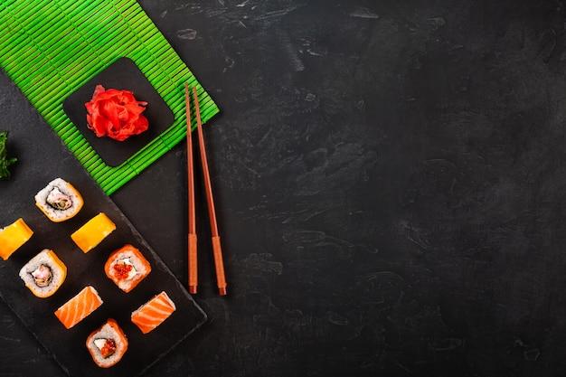 Sushi stellten mit wasabi und ingwer auf schwarzem steinbehälter auf schwarzer tabelle ein. ansicht von oben