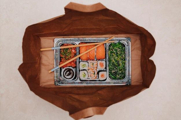 Sushi to go konzept. sammelbox mit sushi. mit sushi-rollen und stäbchen in brauner papiertüte auf dem boden. maki. sashimi. lachs. thunfisch. wasabi. asiatisch. japanisch.