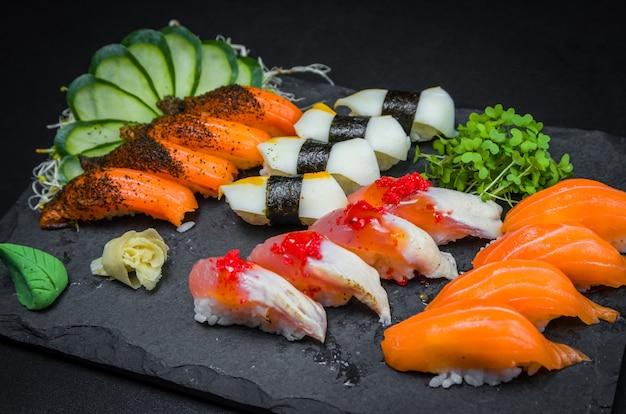 Sushi, traditionelle japanische küche. mehrere leckere sushi auf dem dekorierten teller,