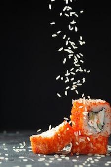 Sushi-turm, kalifornien oder philadelphia-sushi-rollen, mit reissamen bestreut. über schwarzem hintergrund