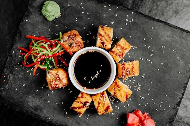 Sushi unagi rollt mit sojasoße und gemüse.