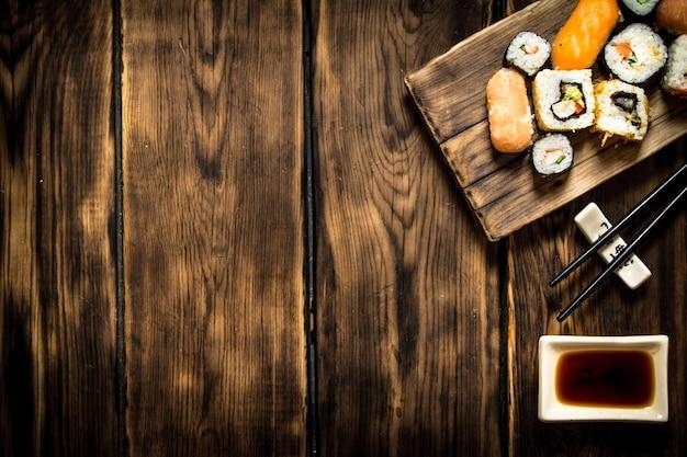 Sushi und brötchen meeresfrüchte mit sojasauce. auf hölzernem hintergrund.