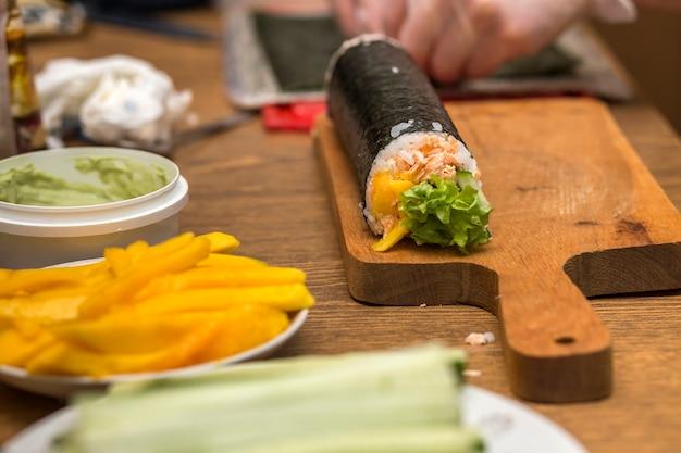 Sushi und brötchen zu hause zubereiten. platten mit bestandteilen für traditionelles japanisches lebensmittel und sushirollen auf hölzernem brett auf küchentisch, ansicht von oben.