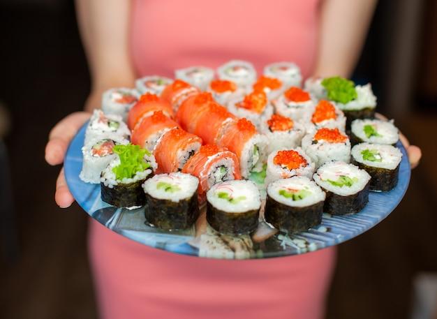 Sushi und brötchen zu hause zubereiten. sushi mit meeresfrüchten, salat und weißem reis. essen für familie und freunde. eine reihe von verschiedenen brötchen und sushi auf einem tablett.