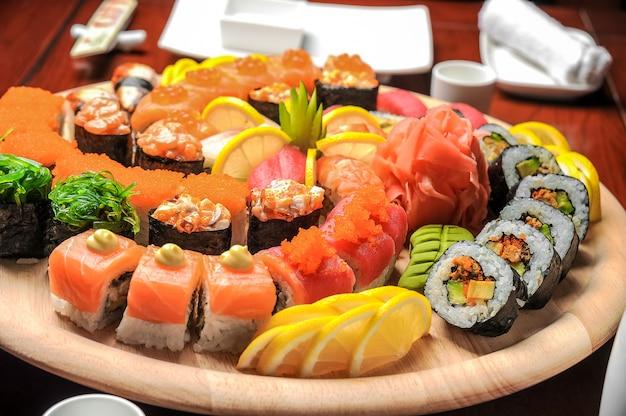 Sushi und rollen nigiri mit fischen dienten auf holztisch