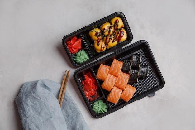 Sushi zum mitnehmen in plastikbehältern, verschiedene brötchen, sojasauce, rosa ingwer, wasabi, sushi-lieferkonzept. bestellung von lebensmitteln