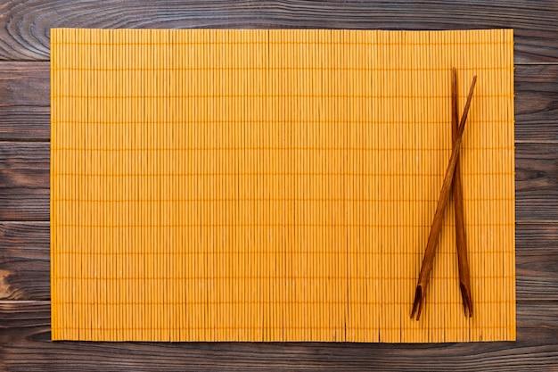 Sushiessstäbchen mit gelber leerer bambusmatte auf hölzernem hintergrund
