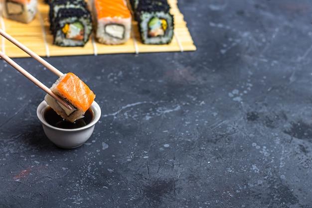 Sushirolle mit lachsen mit essstäbchen über einer schüssel mit sojasoße auf einer dunklen tabelle. traditionelles japanisches essen.
