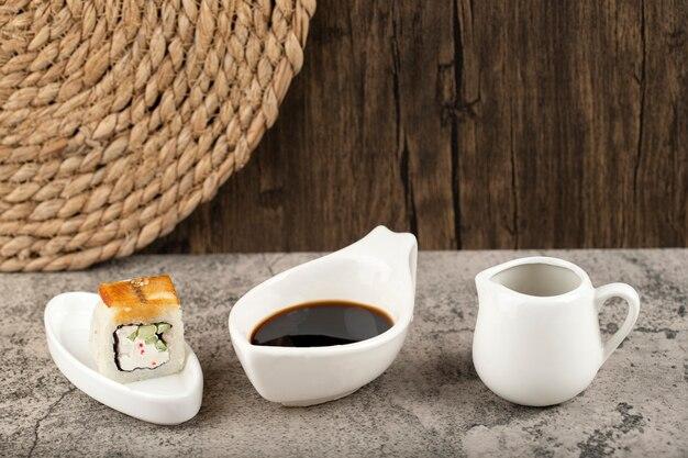 Sushirolle mit sojasauce auf steinhintergrund gelegt.