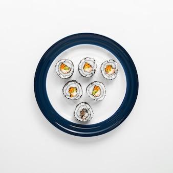 Sushirollen auf blauer und weißer platte