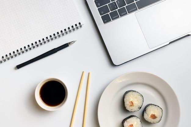 Sushirollen, die bei der arbeit naschen. pause für sushi essen.