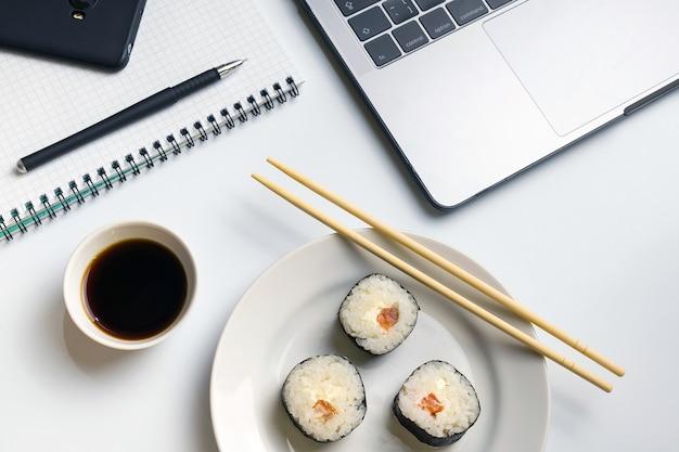 Sushirollen, die bei der arbeit naschen. pause für sushi mit sojasauce.