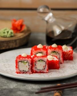 Sushirollen mit den krabbenstöcken und gurke bedeckt mit rotem tobiko