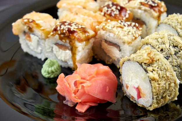 Sushirollen mit ingwer und wasabi auf einem schwarzblech