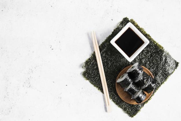 Sushirollen mit sojasoße und essstäbchen auf meerespflanze