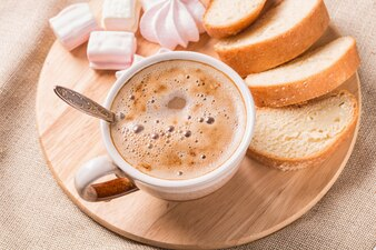 Süße Brötchen, Meringues und Kaffeetasse auf einem Holzbrett