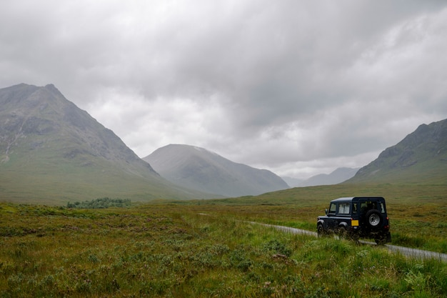 Suv auf einer straße durch die schottischen highlands