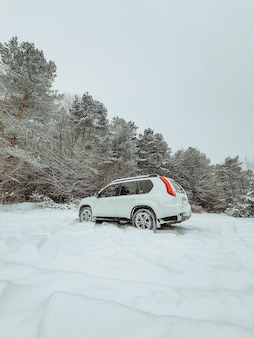 Suv-auto mitten im verschneiten waldkopierraum