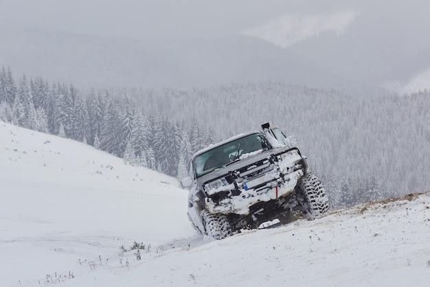 Suv fährt auf einem wintermountian, der gefahr des schnees und des eises fährt und treibt