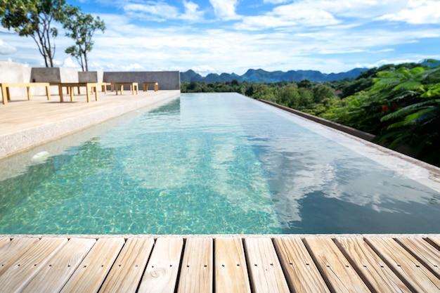 Swimmingpool auf dachdeckgebäude und sonnige reflexionen mit holzfußboden aus teakholz streift sommerferien