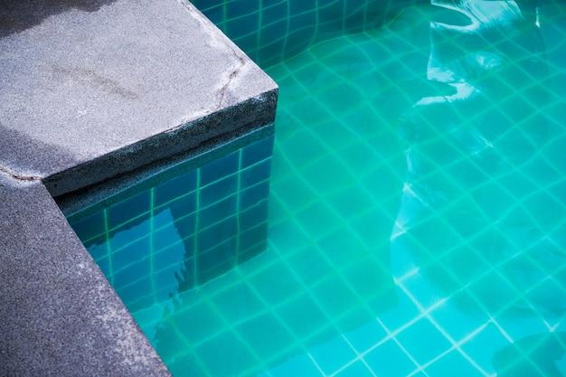 Swimmingpool mit blauem wasser mit blick auf den fliesenboden darunter.