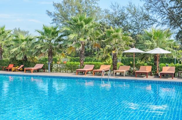 Swimmingpool mit palme, sonnenliegen und weißem sonnenschirm