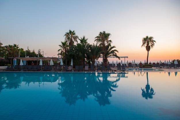 Swimmingpool mit palmen am sonnenuntergang. wasser reflexion